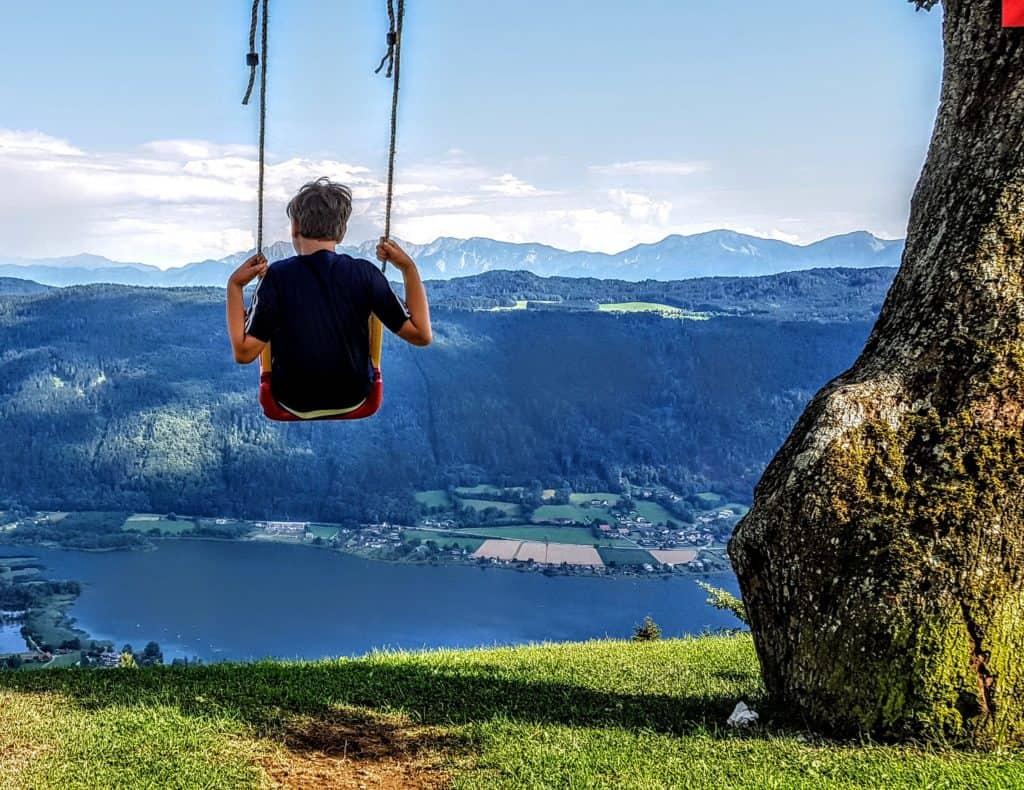 Kind auf Schaukel am Ossiachberg mit Blick auf Ossiacher See und Bleistätter Moor