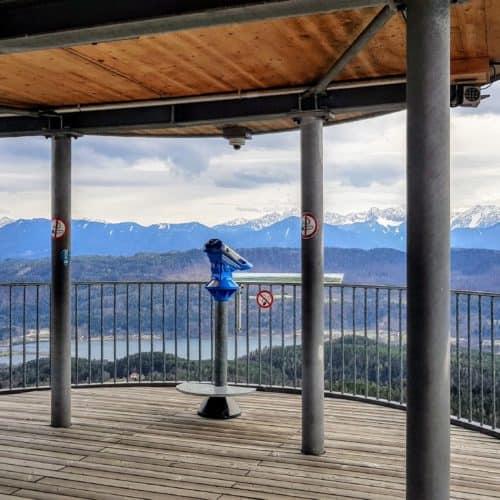 Aussichtsplattform am Pyramidenkogel in Kärnten. Blick auf Keutschacher See und Karawanken. Fernrohr auf Plattform.