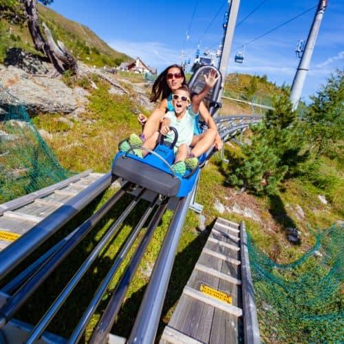 Erwachsene und Kind auf der Sommerrodelbahn Nocky Flitzer auf der Turracher Höhe in Kärnten