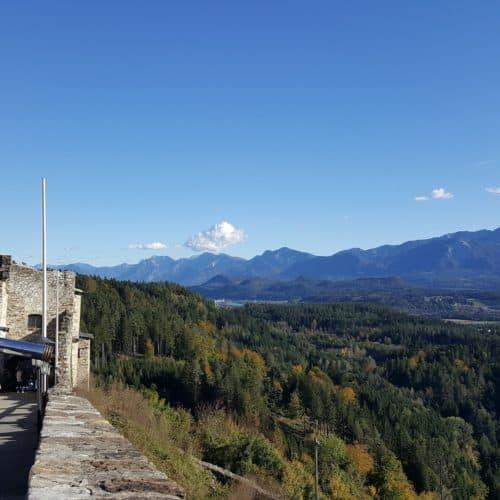 Aussicht auf Karawanken von der Adlerarena Burg Landskron Kärnten. Kind blickt durch Fernrohr