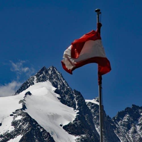 Großglockner mit Österreich-Flagge - auf der Großglockner Hochalpenstraße - eine beliebte Sehenswürdigkeit in Österreich
