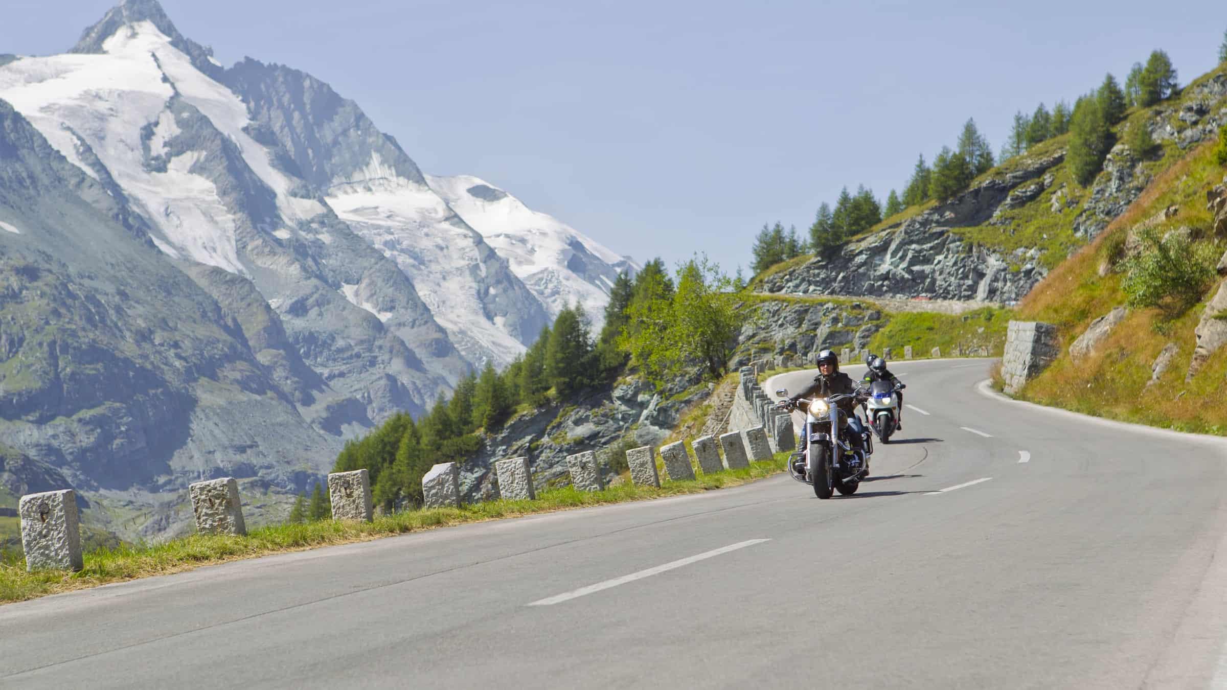 Motorradfahrer entlang der Großglockner Hochalpenstraße mit Großglockner im Hintergrund. Schönste Panoramastraße in Österreich.