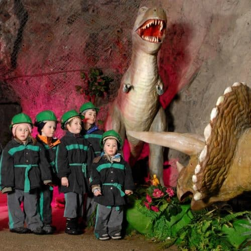 Kinder mit Dinosaurier im Schaubergwerk Terra Mystica in Bad Bleiberg Kärnten - Österreich