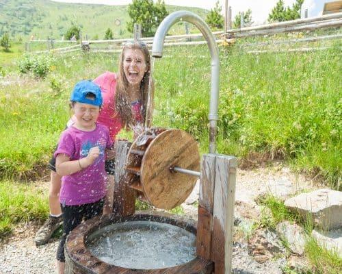 Spielende Familie am Wasserspielplatz in der Kindererlebniswelt Nocky's Almzeit auf der Turracher Höhe - Österreich