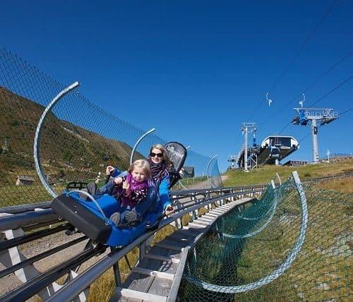Sommer Rodelbahn Nocky Flitzer auf der Turracher Höhe in Kärnten. Erwachsene mit Kind auf der rasanten Attraktion.