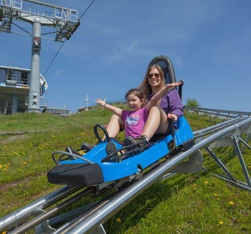 Kind mit Eltern auf der Sommerrodelbahn Nocky Flitzer auf der Turracher Höhe in Kärnten und Steiermark in Österreich