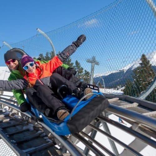 Nocky Flitzer Turracher Höhe Rodelbahn TOP 10 Ausflugsziele Kärnten Steiermark im Winter. Vater mit Kind beim Rodeln.