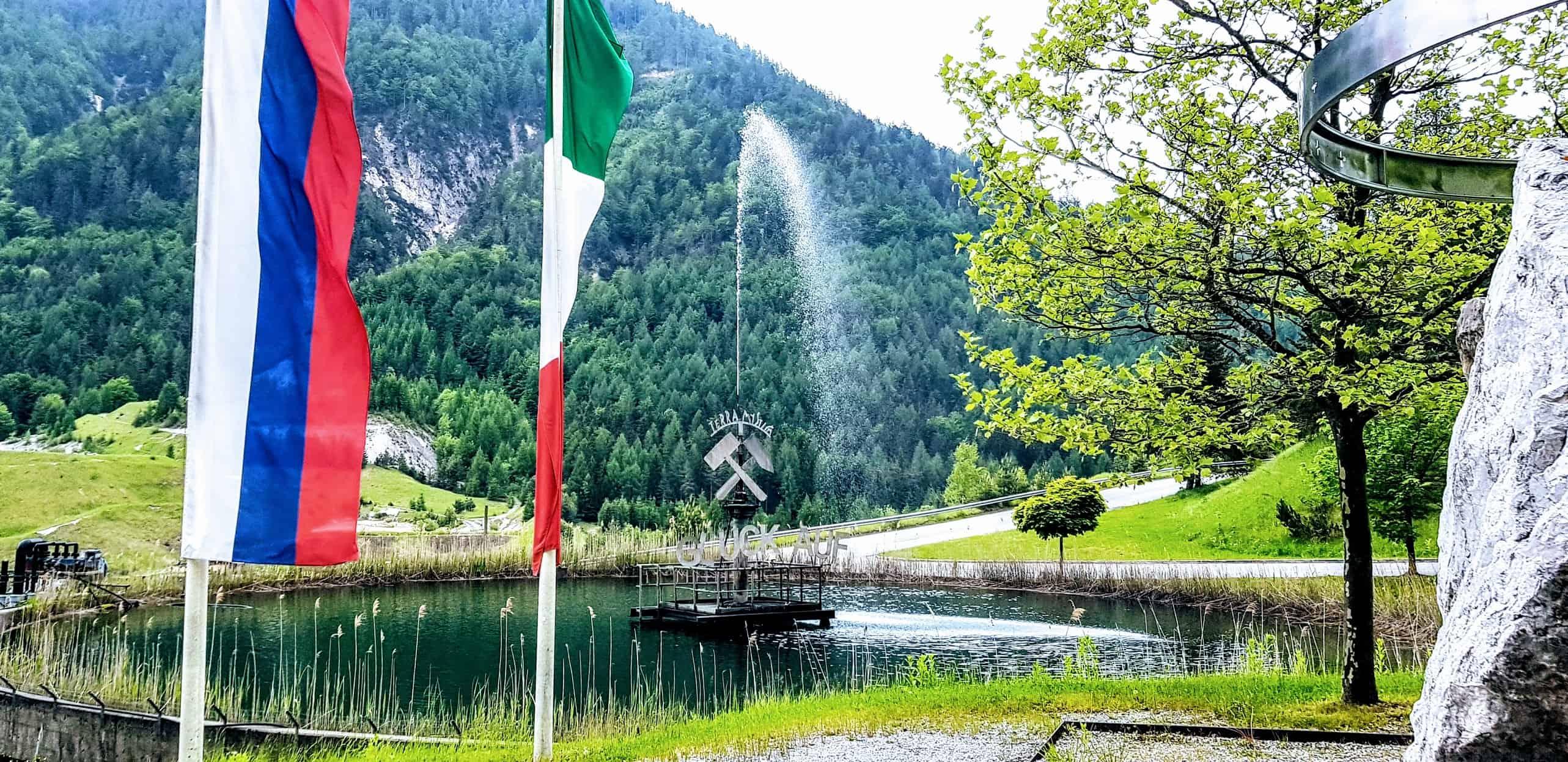 Teich mit Brunnen und Fahnen vor Schaubergwerk Terra Mystica im Naturpark Dobratsch