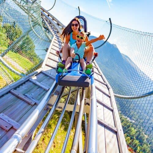 Auf der Alpen-Rodelbahn Nocky Flitzer auf der Turracher Höhe in Kärnten. Erwachsene mit Kind flitzen vom Berg ins Tal.