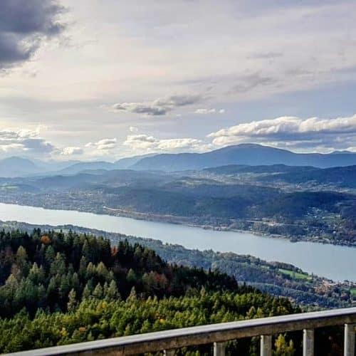 Wörthersee mit Velden im Herbst vom Ausflugsziel Pyramidenkogel. Im Hintergrund Dobratsch und Nockberge. Urlaub in Kärnten.