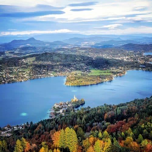 Traumhafter Blick auf Maria Wörth vom Pyramidenkogel in Kärnten am Wörthersee bei Herbsturlaub. Blätter sind bereits bunt.