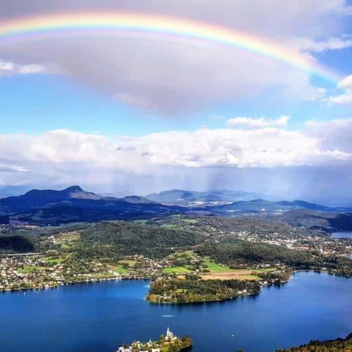 Regenbogen über Wörthersee bei Ausflug auf Pyramidenkogel. Blick auf Klagenfurt, Maria Wörth, Krumpendorf, Pörtschach, Berge. Sehenswürdigkeit in Österreich.