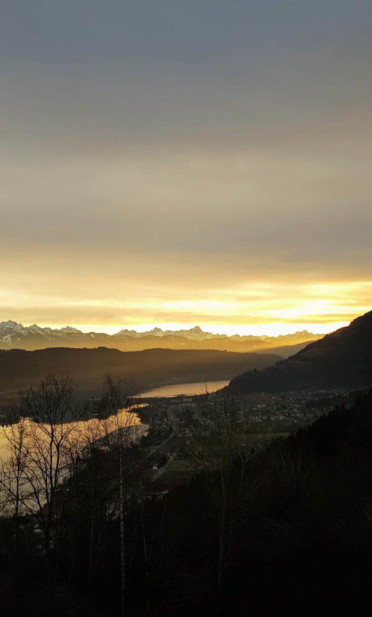 Panorama mit Sonnenuntergang am Wanderweg über den Ossiacher See und Steindorf in der Region Villach in Kärnten, Österreich.