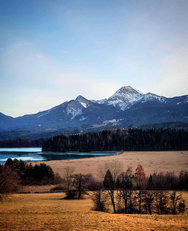 Winter in Kärnten in der Region Villach mit Blick auf Faaker See, Mittagskogel und Karawanken. Radtour um den See.