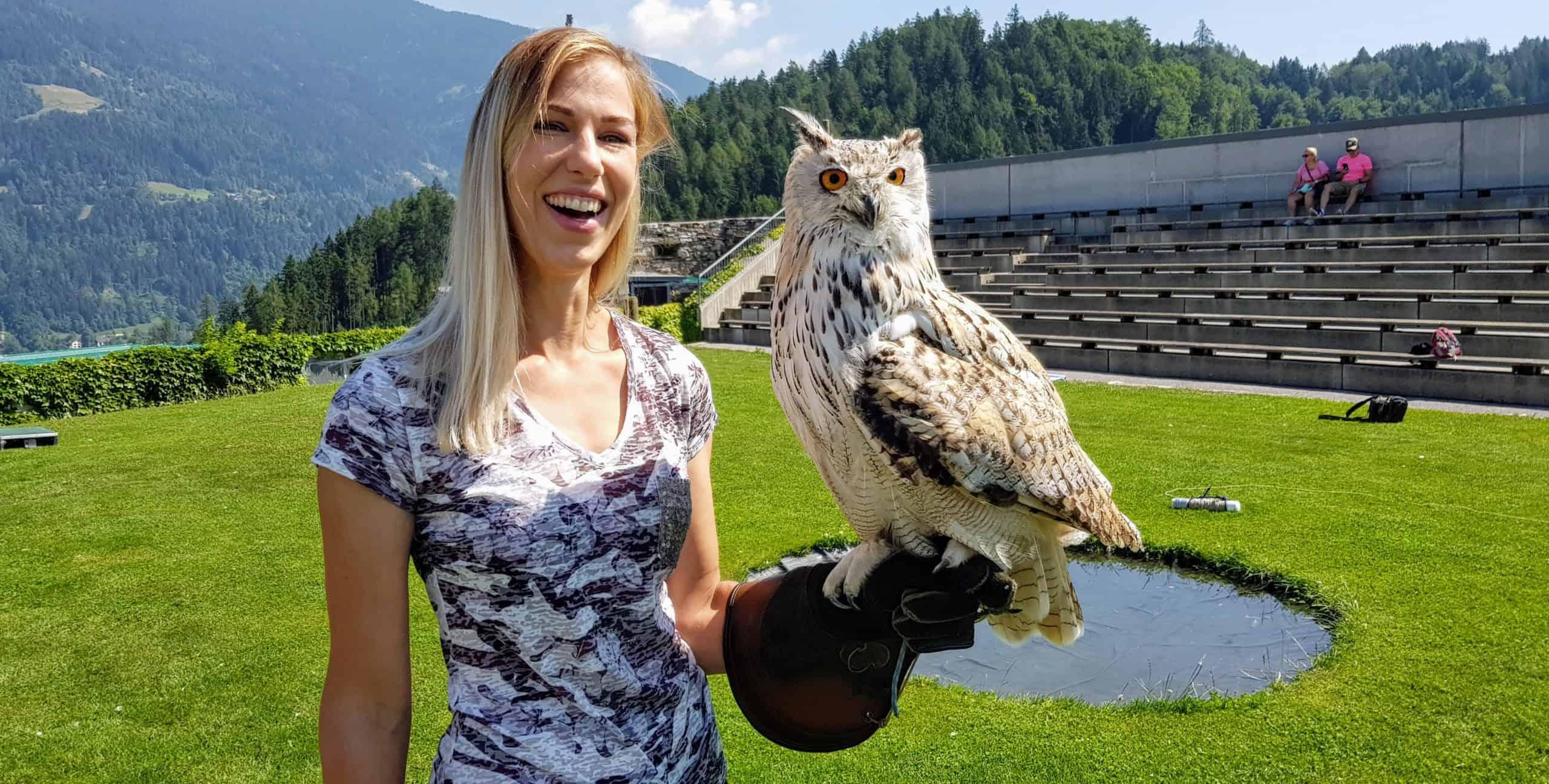 Sibirischer Uhu mit Besucherin auf der Adlerarena Burg Landskron in Kärnten am Ossiacher See bei Urlaub in Villach, Österreich