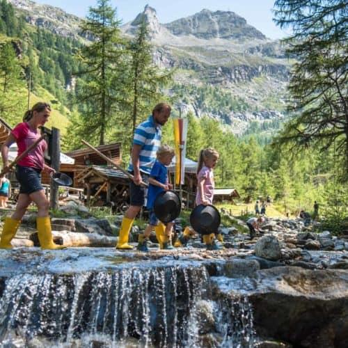 Familie beim Goldgraben im Goldgräberdorf Heiligenblut Nahe Großglockner in Kärnten. Ausflugsziele mit Kindern in Österreich.
