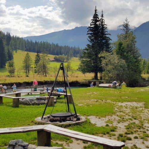Kinder und Erwachsene am Kinderspielplatz bei Fluss in Mallnitz, Start Seebachtal Wanderungen. Ausflugstipp für Kärnten mit Kindern.