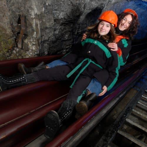 Sehenswürdigkeit Schaubergwerk Terra Mystica bei Villach im Winter geöffnet - Familie mit Kind auf Bergmannsrutsche