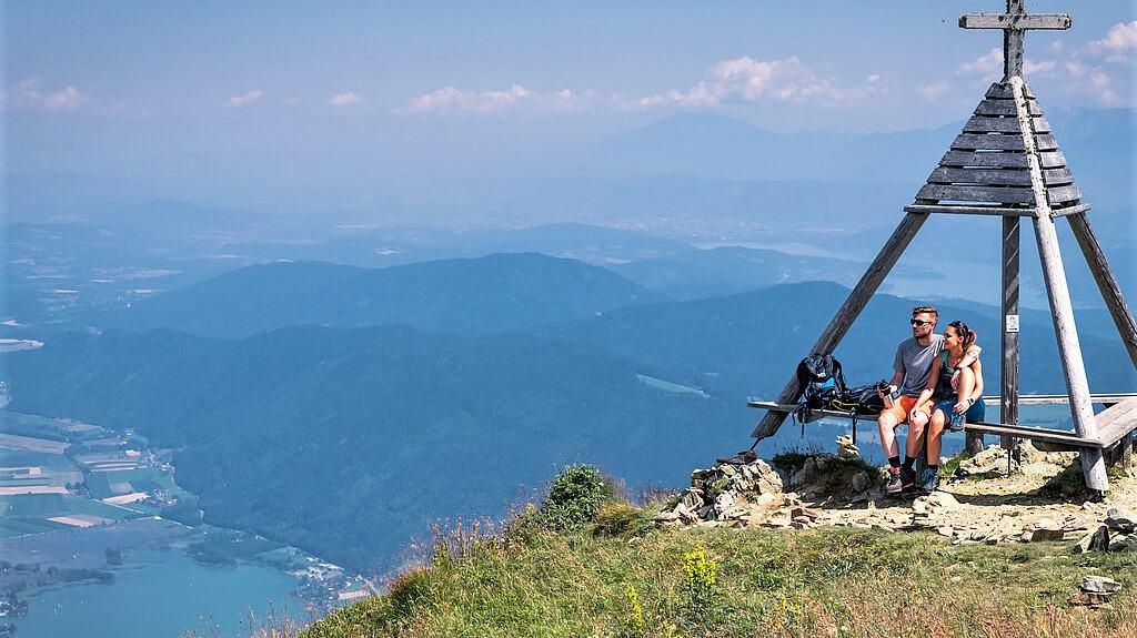 Geheimtipps & schöne Orte in Kärnten: Wanderer auf der Gerlitzen Alpe mit Blick auf Ossiacher See, Bleistätter Moor & Karawanken