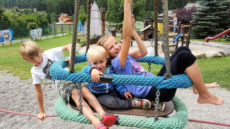 Kinder auf Spielgerät im Outdoor Kinderspielplatz im Maltatal beim Fallbach, Kärntens höchster Wasserfall